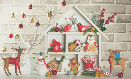 Christmas scene with white wooden house, presents, cookies, snowman and deers
