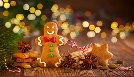 クリスマスの手作りジンジャーブレッド クッキーと木製の背景にスパイス