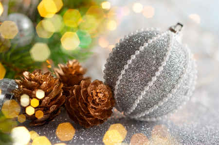 Christmas concept with silver bauble, fir cones and festive fir tree