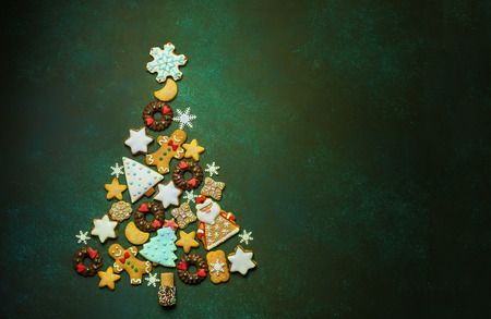 Assorted Christmas cookies in the shape of a Christmas tree on the dark green background. Top view.