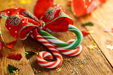Christmas Candy canes with a gift ribbon on the wooden background