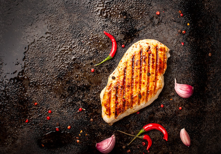 Spicy grilled chicken breast with chilli and garlic on a roasting tin. Reklamní fotografie