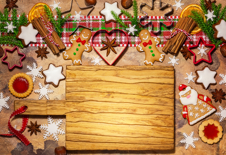 Christmas baking background with assorted Christmas cookies, spices, cookie molds and wooden cutting board. Top view. Stock Photo