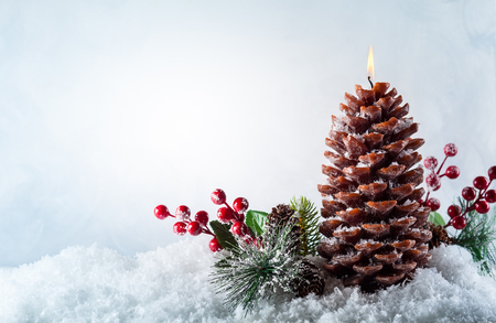 Christmas candle in shape pine cone on the snow background 版權商用圖片