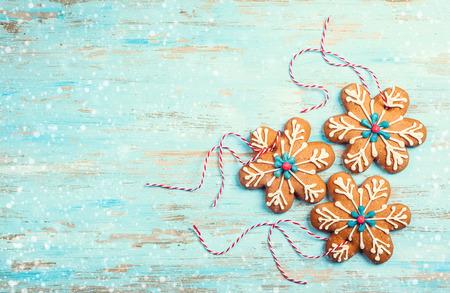 Piernikowe płatki śniegu na Boże Narodzenie na niebieskim drewnianym tle