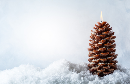 Christmas candle in shape pine cone on the snow background Stock fotó