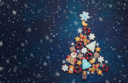 Assorted Christmas cookies in the shape of a Christmas tree on the blue background. Top view.