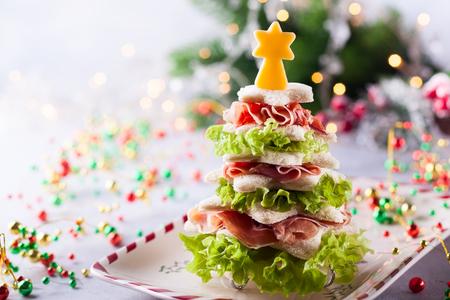 Weihnachtsbaum aus geröstetem Brot, Salat, Schinken und Käse. Festliche Idee für Weihnachten oder Silvester.