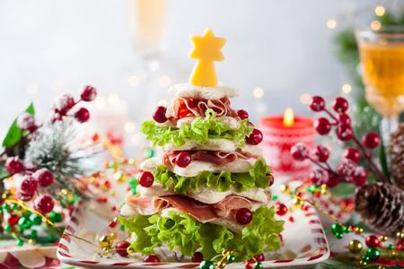 Árbol de Navidad de pan tostado, lechuga, jamón y queso. Idea festiva para la cena de Navidad o Año Nuevo. Foto de archivo