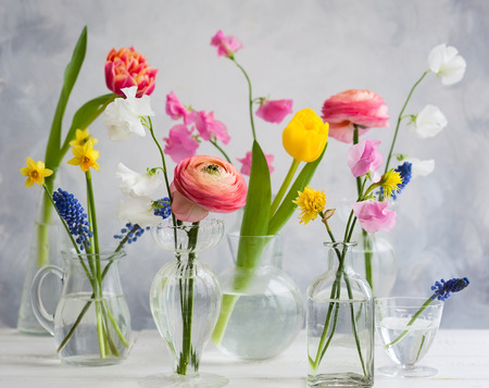 Beautiful flowers bouquets in glass vases on the wooden table.Tulips,roses,muscari, narcissus, eustoma and hyacinths