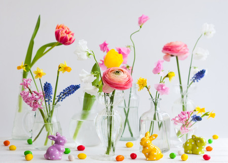 Beautiful flowers bouquets in glass vases on festive Easter table. Colored Easter eggs in egg cups
