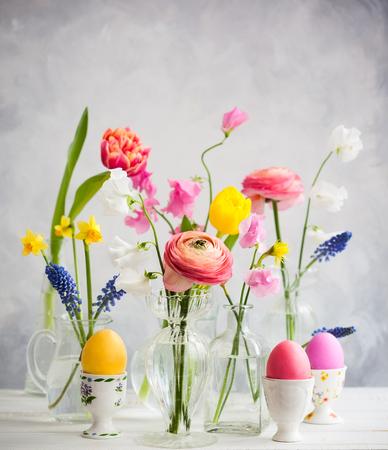 Schöne Blumenblumensträuße in den Glasvasen auf festlicher Ostern-Tabelle. Farbige Ostereier in Eierbechern.