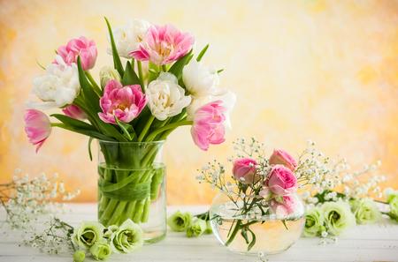 Ramo de flores hermosas en florero sobre la mesa de madera. Tulipanes, rosas y eustoma. Foto de archivo
