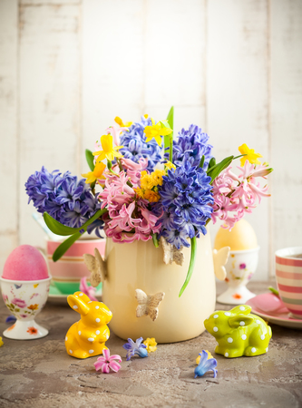 Easter breakfast table with tea,eggs in egg cups, spring flowers in vase and Easter decor Stock Photo