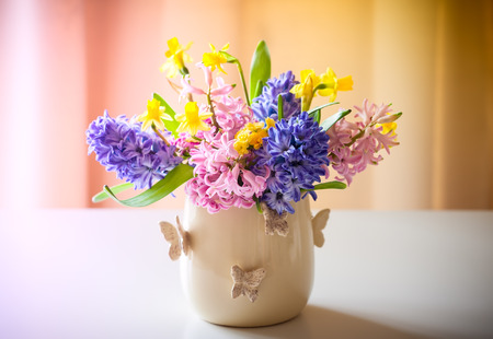 Fresh beautiful spring flowers in vase on  table. Easter decoration for home.