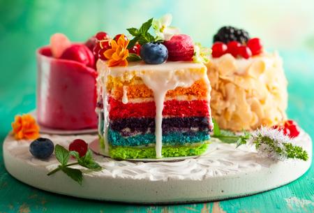 흰색 트레이에 케이크의 다양 한 조각 : 무지개 케이크, 라스베리 케이크와 아몬드 케이크. 휴일을위한 신선한 딸기와 꽃으로 장식 된 과자 스톡 콘텐츠