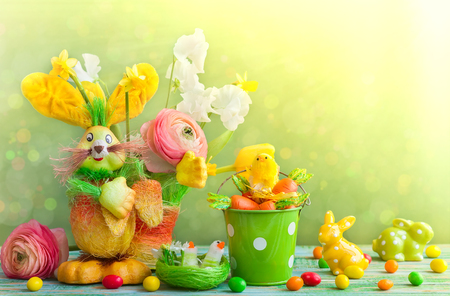 Easter holiday decorations with bunny, chicks, chocolate eggs and spring flowers