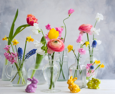 Beautiful flowers bouquets in glass vases on festive Easter table. Colored Easter eggs in egg cups Banque d'images - 95365054