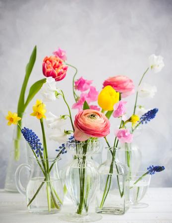 木製のテーブルの上のガラスの花瓶に美しい花の花束。チューリップ、バラ、ムスカリ、ナルキッソス、エウストーマ、ヒヤシンス