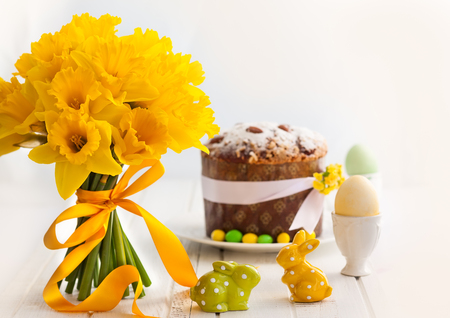 Easter bouquet of yellow daffodils and Easter cake on white wooden table. Easter concept of festive breakfast.