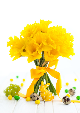 Easter bouquet of yellow daffodils with ribbon and Easter decor on white wooden table. Easter concept with copy space. Stockfoto