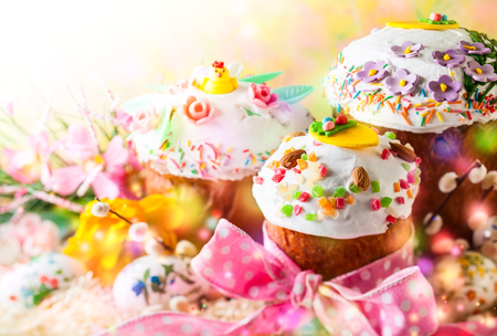 Various Spring Easter cakes with white icing and sugar decor on the table decorated in rustic style Stock Photo