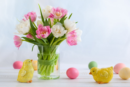 Easter bouquet of spring tulips and Easter eggs and decor on white wooden table. Easter concept with copy space. Stockfoto