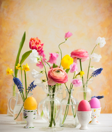 Beautiful flowers bouquets in glass vases on festive Easter table. Colored Easter eggs in egg cups 스톡 콘텐츠