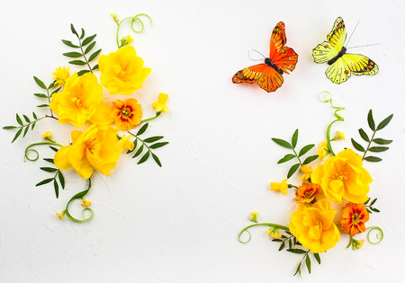 Flowers composition oh white background with spring flowers and butterfly. Easter concept with copy spase. Flat lay, top view.