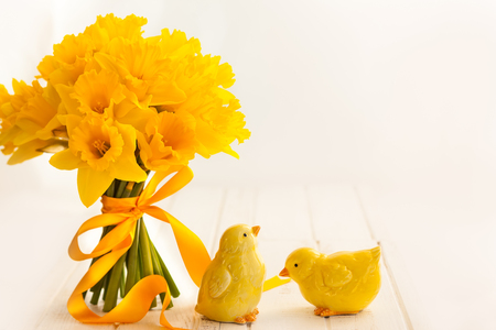 Easter bouquet of yellow daffodils with ribbon on white wooden table. Easter concept with copy space. Stock Photo