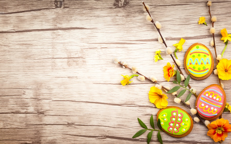 Easter composition with spring flowers and easter cookies on wooden background. Easter concept with copy space. Flat lay, top view.