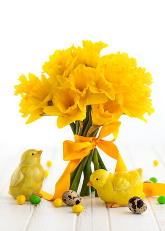 Easter bouquet of yellow daffodils with ribbon and Easter decor on white wooden table. Easter concept with copy space. Stock Photo