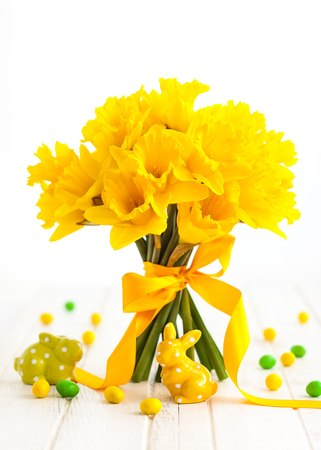 Easter bouquet of yellow daffodils with ribbon and Easter decor on white wooden table. Easter concept with copy space. Standard-Bild