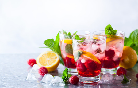 Raspberry lemonade in glasses with fresh berries and mint leaves