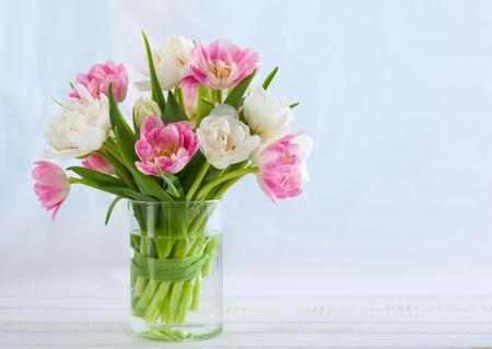 Ramo fresco de tulipanes de la primavera en la mesa de madera blanca. Foto de archivo