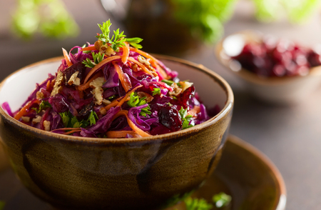 Red cabbage, carrot, apple salad with nuts and cranberry. Coleslaw for autumn or winter season.