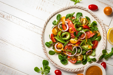 Smoked salmon, avocado and cherry tomatoes salad with honey mustard dressing. Healthy salad in plate on a wooden table. Top view