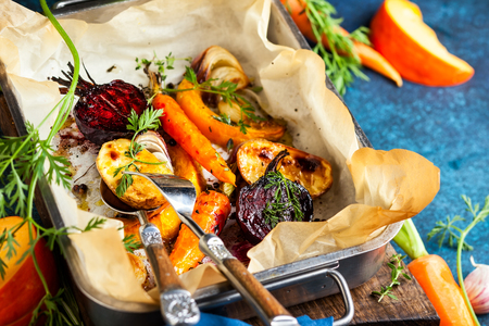 Oven Roasted vegetables with garlic and herbs on the baking tray. Autumn-winter root vegetables.