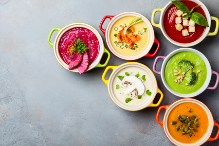 Variety of colorful vegetables cream soups in small pots. Top view. Concept of healthy eating or vegetarian food. Banco de Imagens