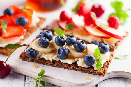Healthy sandwiches with berry, honey and cream cheese on white wooden boar Stock Photo