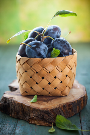 Fresh plums with leaves in basket on wooden background