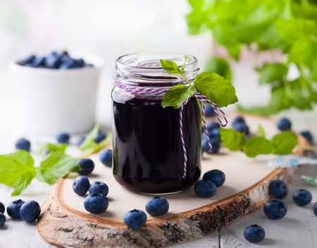 Blueberry homemade jam in glass jar and fresh berries