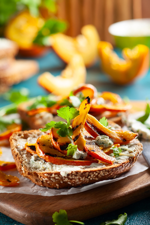 Open sandwich with grilled pumpkin and soft cheese  on multigrain rye bread. Stock Photo