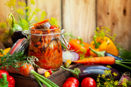 Homemade preserved from eggplant with vegetables in glass jar -ratatouille. Fall preserved vegetarian food concept, copy space.