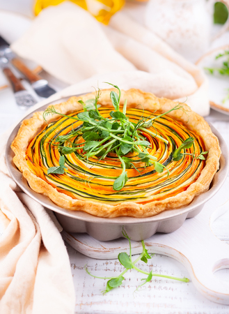 Homemade vegetable tart with carrot, zucchini and pumpkin on white wooden table. Spiral vegetable tart.