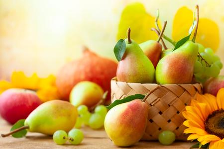 Bodegón otoñal con frutas de temporada, flores y verduras sobre fondo de madera.