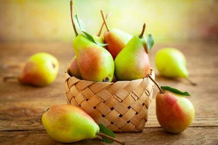 Fresh ripe pears in basket on the wooden table. Organic fruits, concept of healthy eating with copy space.