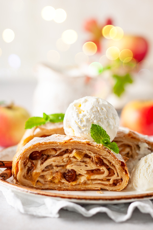 Traditional pieces of apple strudel with cinnamon,raisin, powdered sugar and  vanilla ice cream. Stock Photo