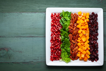 Autumn-winter season salad with roasted pumpkin, dried cranberry, pecan and pomegranate seeds.