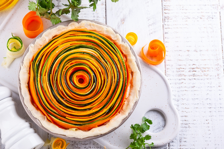 Preparing homemade vegetable tart with carrot, zucchini and pumpkin on white wooden table. Spiral vegetable tart. Stockfoto
